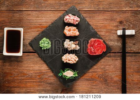 Fresh delicious set of five gunkan sushi served on black slate with ginger and wasabi, on wooden rustic table, flat lay. Tasty seafood, gourmet delicacy. Japanese cuisine.