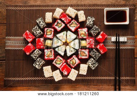 Colorful delicious set of sushi served on brown straw mat, flat lay. Food art, beautiful ornament. Japanese cuisine, restaurant menu photo.