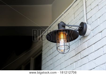 vintage style hang wall light bulb cafe decoration outdoor on white brick wall.