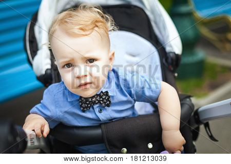 kid sitting in stroller. baby for a walk in a pram. spring outdoors. Child in buggy Little kid in pushchair. Transportation for family with infant
