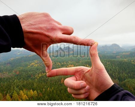 Close up hands make frame gesture. Melancholy misty valley bellow rocky peak. Cold spring daybreak in mountains.