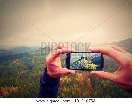 Smart Phone Mobile Photography Of Misty Landscape. Focus To Detail With Phone In Man Hands.