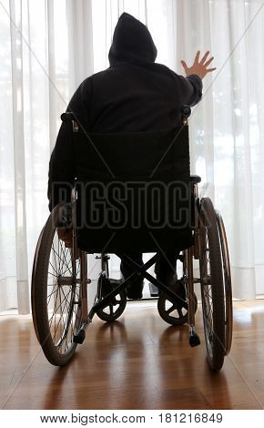 handicapped man in a wheelchair in his bedroom