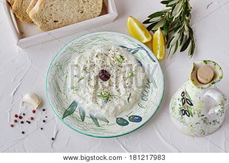 Homemade Greek traditional sauce tzatziki with cucumber, garlic, yogurt and lemon in a bowl and jar with olive oil on a abstract background. Healthy eating concept. Mediterranean lifestyle