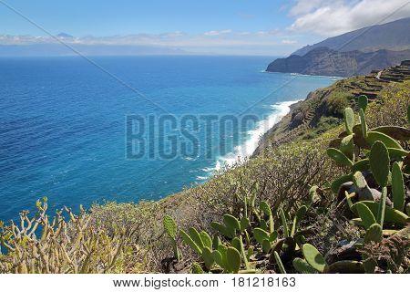 AGULO, LA GOMERA, SPAIN: The wild Atlantic coast near Agulo with the Atlantic Ocean and Teide volcano (in Tenerife Island) in the background