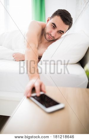 Young Man In White Atmosphere Close The Alarm Off Of His Phone In The Morning