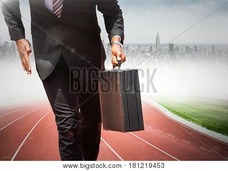 Digital composite of Business man lower body with briefcase on track against blurry skyline