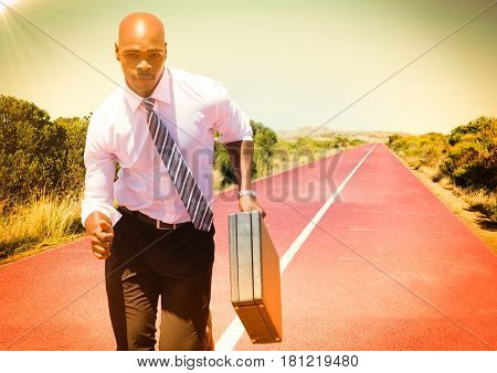 Digital composite of Business man running with briefcase on track in desert with flare
