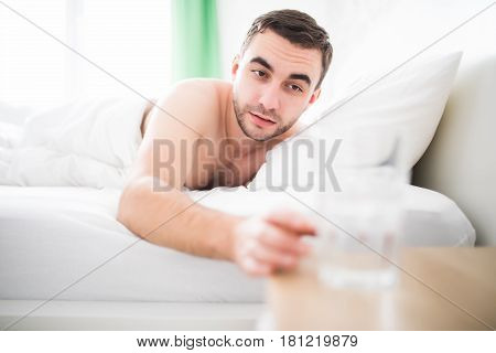 Handsome Man Wake Up In The Morning In Her Bed And Extend To Glass With Water.