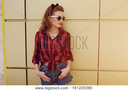 beautiful girl, brightly dressed in the style of pin-up walks in with glasses