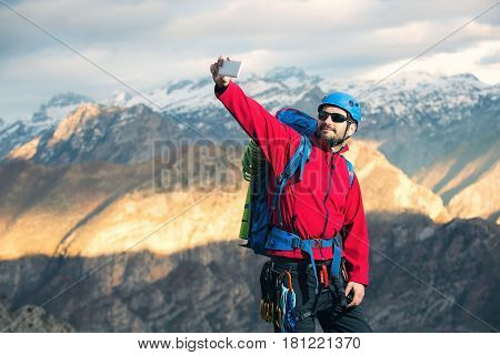 Young mountaineers standing on top of a mountain and make selfie photo