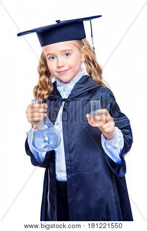 Portrait of a cute nine year old girl in an academic gown and hat holding beakers. Educational concept. Isolated over white.