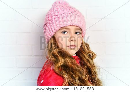 Winter clothes concept. Pretty smiling girl with long curly hair wearing pink knitted hat and smiling at camera.