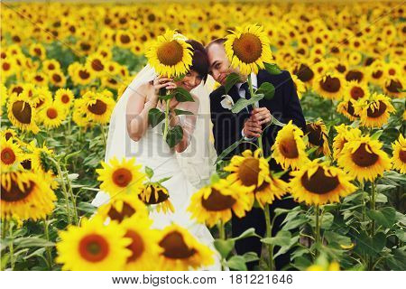 Funny Married Couple Pose On The Field Holding Sunflowers In Their Hands