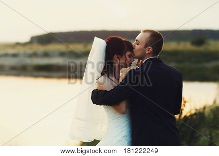 Groom Kisses Bride's Forehead Standing With Her On The Lake's Shore