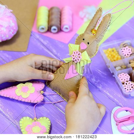Little girl holds a felt Easter bunny toy in hands. Girl shows a felt bunny with hearts. Handmade Easter gift. Tools and materials for kids creativity on a wood table. Fun crafts project for children