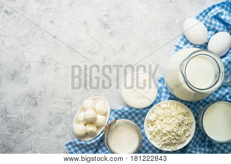 Selection of Dairy products. Cottage cheese or curd, yogurt, Sour cream, milk, eggs and mozzarella at concrete table. Top view