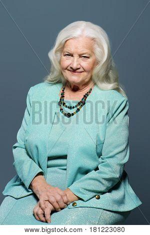 Portrait of a modern senior woman with beautiful blonde hair. Studio shot. Beauty, fashion.