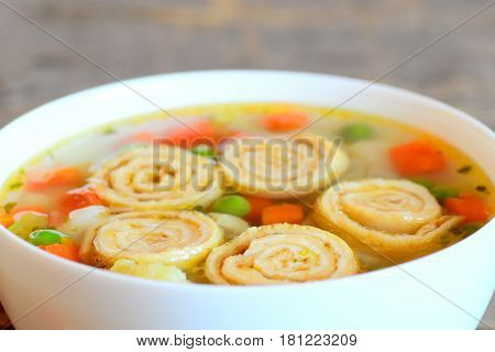 Vegetable soup with omelet rolls in a bowl on rustic wooden table. Diet soup with omelet, carrot, peas, leek, cauliflower and potatoes. Closeup