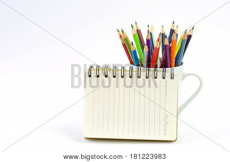 Color pencil and sketchbook on white background