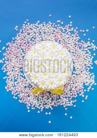 Cake with sugar paste flowers, on blue background