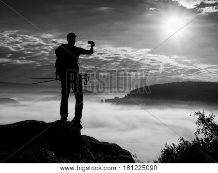 Strong Man Hiker Taking Photo With Smart Phone At Mountain Peak.