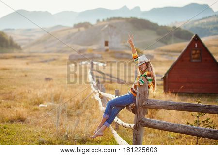 happy woman posing in cowboy hat at countryside
