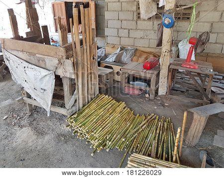 Thai traditonal factory making wooden handle of grass broom