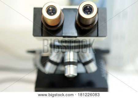 A woman and a man study the structure of the drug pellets under a microscope. The quality of the powder granules of the suspension when magnified under a microscope. Laboratory of Quality Pharmaceutical Plant.
