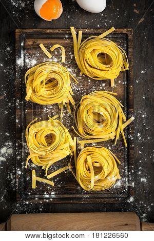 Fresh italian raw homemade pasta tagliatelle at wooden table. Italian food background.