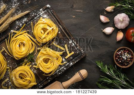 Fresh italian pasta tagliatelle at wooden table and ingredients for cooking. Italian food background.
