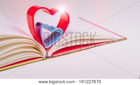 Red and blue hearts over diary book on white table light flares on the top of the heart.