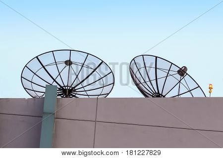 Satellite dish and lightning rod on the building against blue sky with copy space