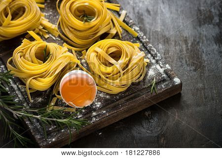 Fresh italian raw homemade pasta tagliatelle at wooden table. Close up copy space.