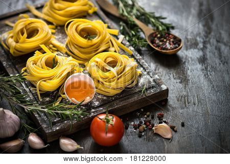Fresh raw pasta tagliatelle and ingredients for cooking. Italian food background.
