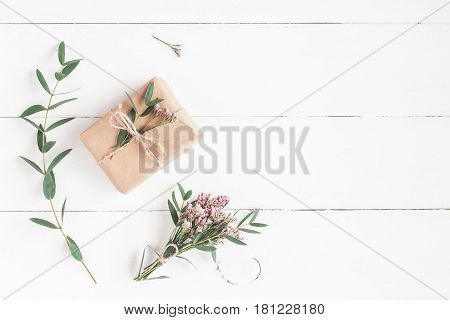 Flowers composition. Gift pink flowers and eucalyptus branches on white wooden background. Flat lay top view
