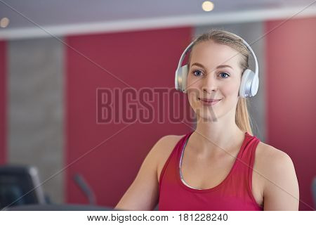 Smiling young blond woman wearing headphone in gym