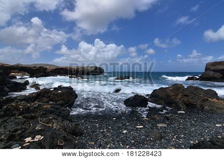 Beautiful look at the lava rock and horizon on Aruba's black sand stone beach.