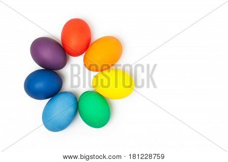 Colored easter eggs on white background. Seven eggs laid out in the order of the colors of the rainbow in the form of a flower. Place for text. Flat lay