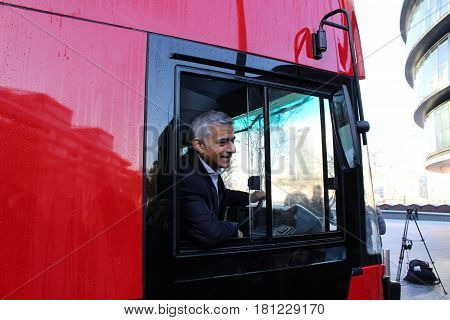 London, November 2016. Sadiq Khan, Mayor of London, poses with a red London double decker bus outside City Hall in Southwark, South London