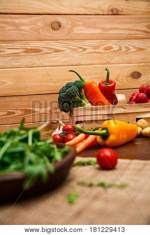 Sweet pepper, brocoli and cherry tomatoes. Potatoes, garlic and red radish. Natural raw vegetables. Organic bio food on rustic wooden table.