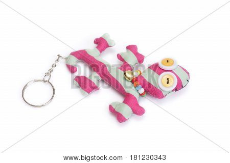 Handmade cute gecko keychain on white background.