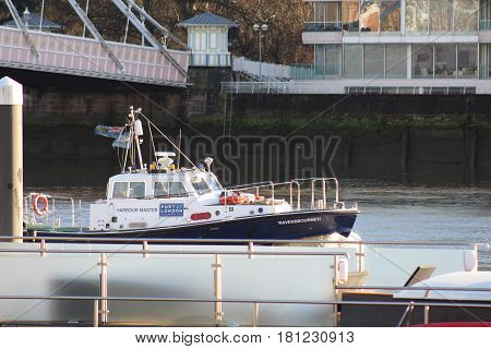 London, December 2016. A Port of London motorboat travels along the River Thames in London