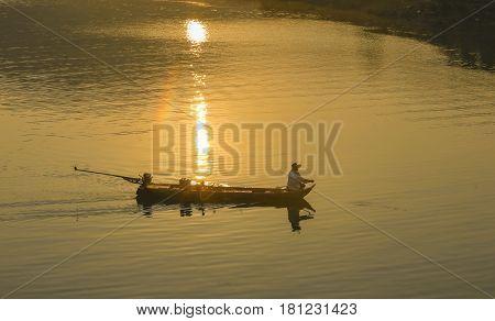 Dak Lak, Vietnam, March 12, 2017: Fishing man on boat In Sunlight in river