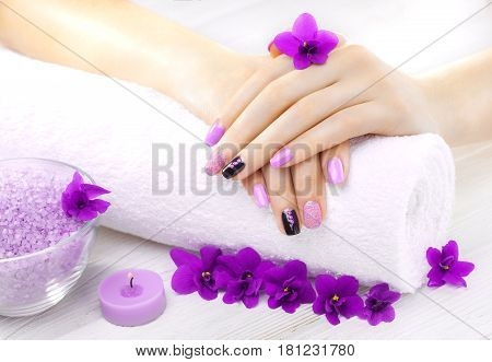 beautiful purple manicure with violet, candle and towel on the white wooden table. spa