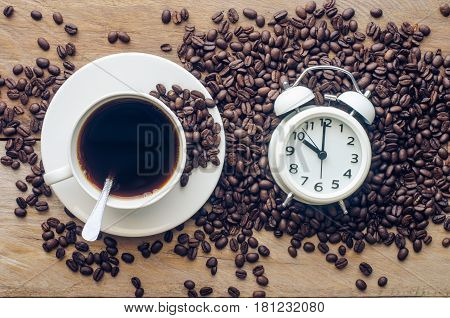 Coffee and coffee beans are placed near the alarm clock - concept articles useful as well