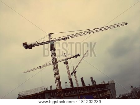 Three building cranes against the background of a rainy gray sky. Metal cranes bottom view. Construction cranes silhouettes against cloudy sky. Construction site. Warm tone