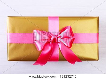 Gift box with pink bow. Present wrapped with ribbon. Christmas or birthday golden paper package. On white wooden table.