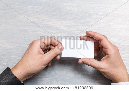 Hand hold blank business card design mockup. Businessman holding visiting card. Business branding template. Person in suit and white shirt.