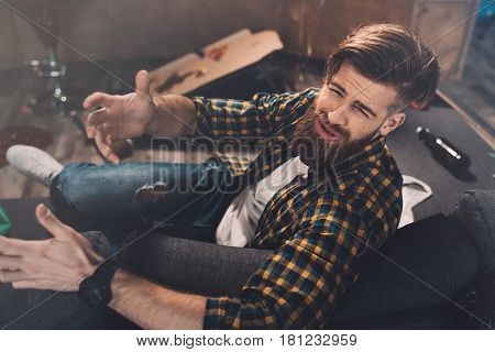 Upset Bearded Young Man With Hangover Gesturing In Messy Room After Party